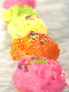 Line of cupcakes with various shades of icing and sprinkles