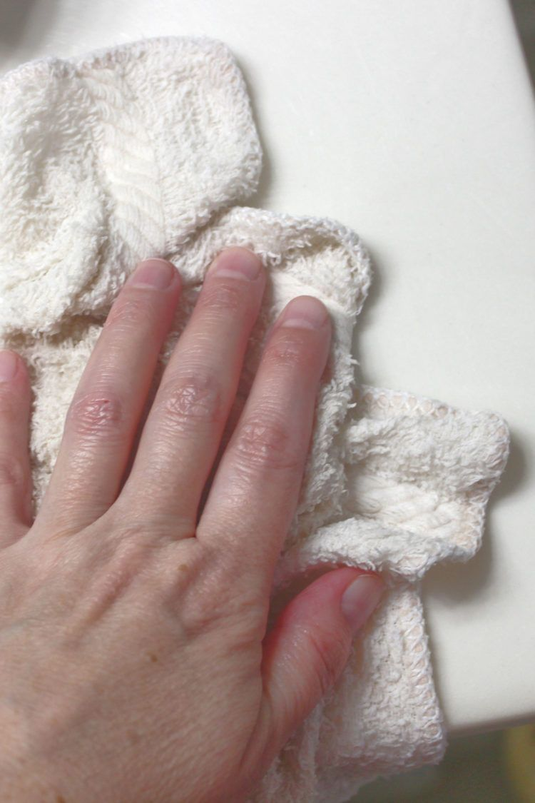 Hand with washcloth cleaning surface with water