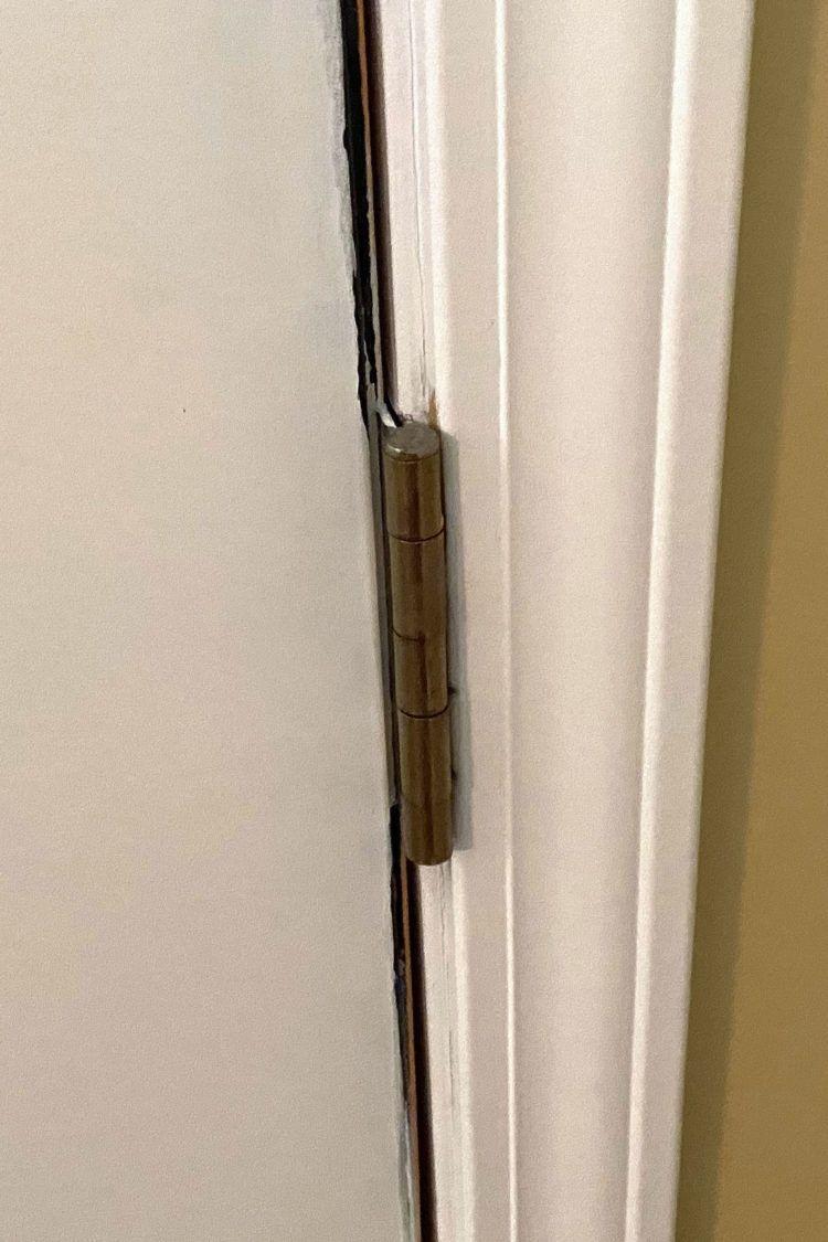 Closeup of door hinge on inside of front home door