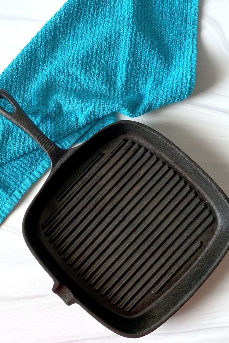 Square cast iron skillet grill beside dish towel