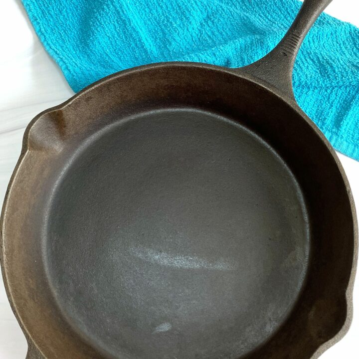 Cast iron skillet on table with blue dish towel