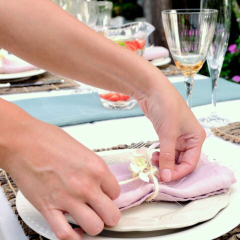 Close up of hands setting outdoor party table in garden