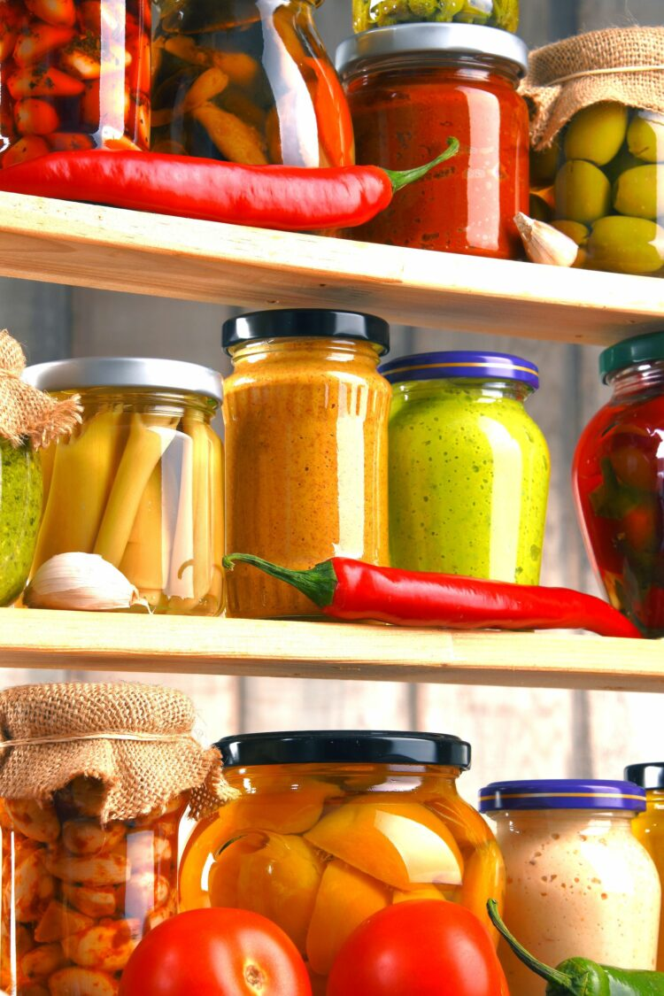Pantry staples including jars and vegetables on shelves