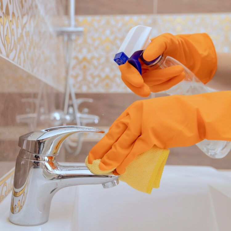 Gloved hands cleaning faucet