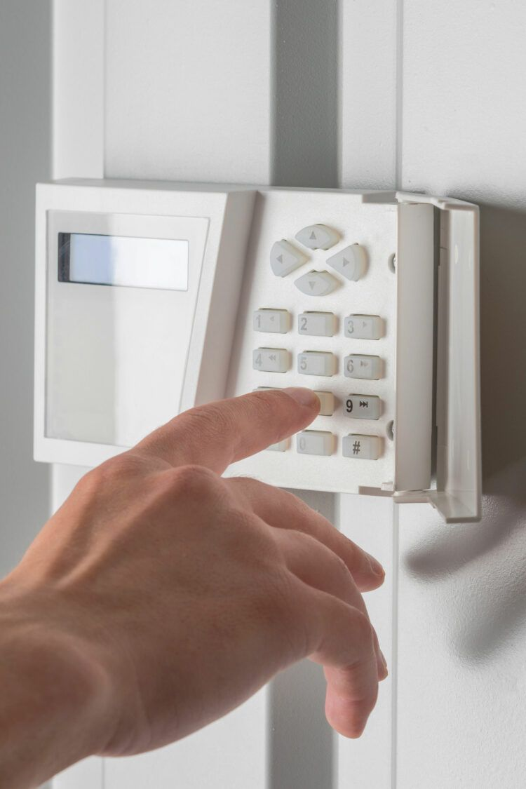 Hand pressing buttons on home security code system